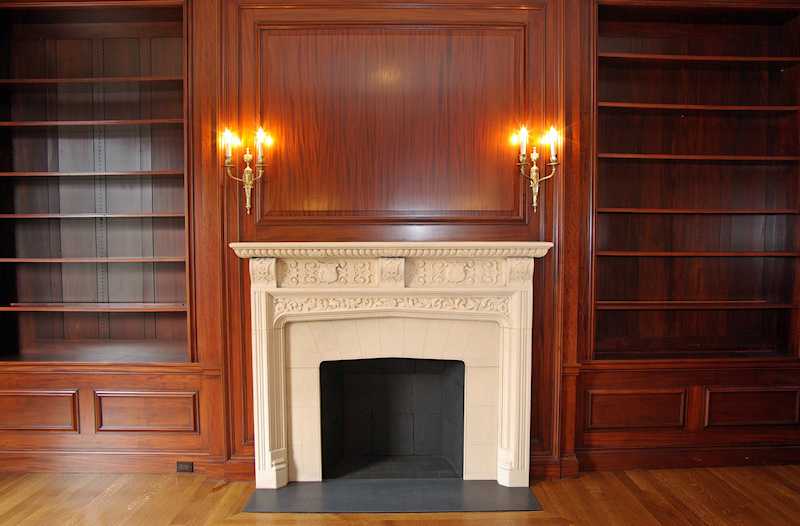 Book case flanked Limestone Fireplace