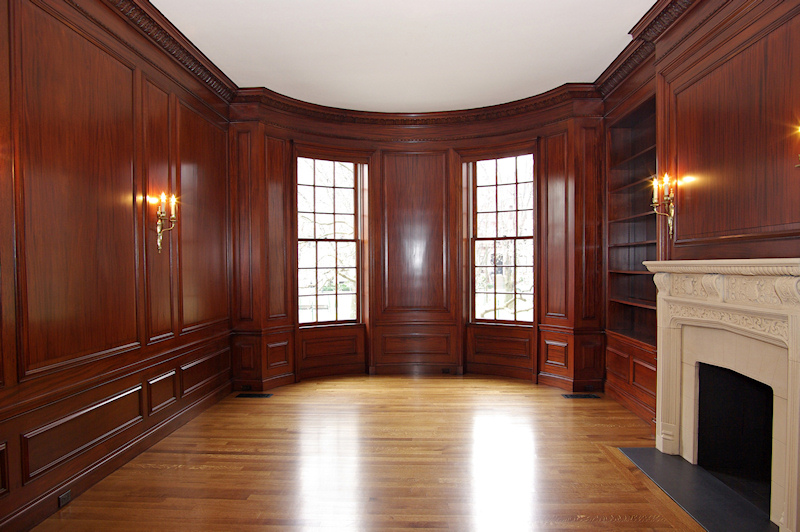 library with mahogany paneling and limestone fireplace
