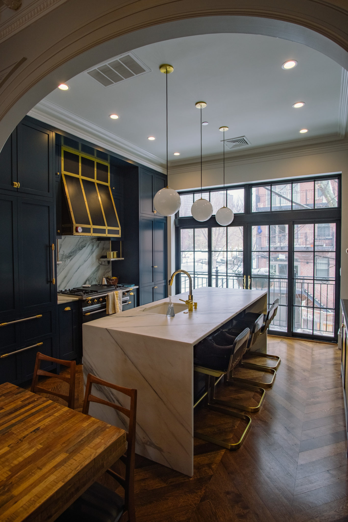 Kitchen with high ceilings, recessed lighting, french stove and vent, waterfall island